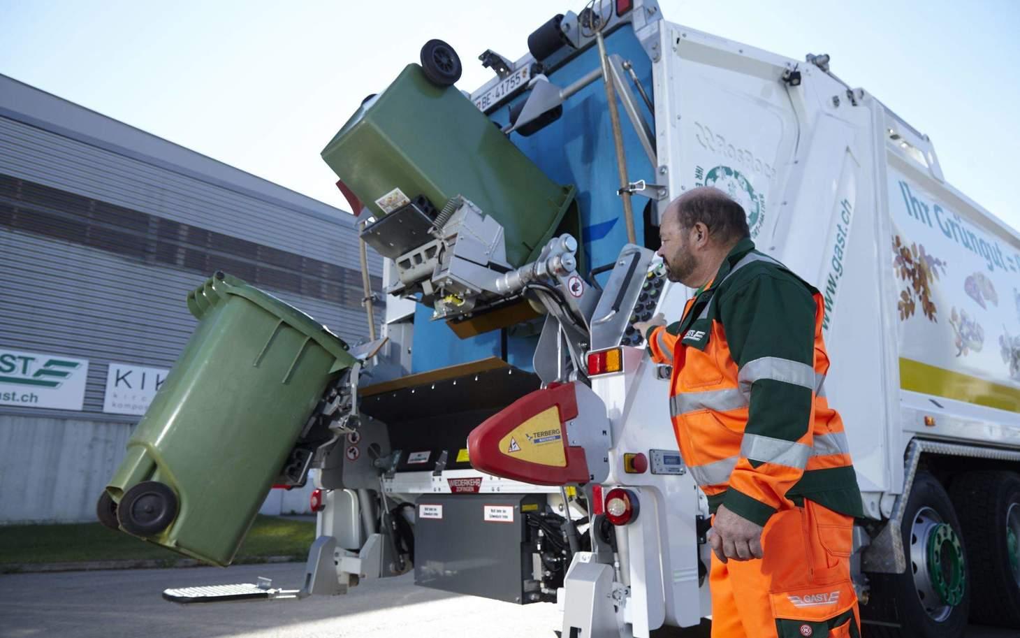 Mitarbeiter leert Grüncontainer in Ghüderwagen