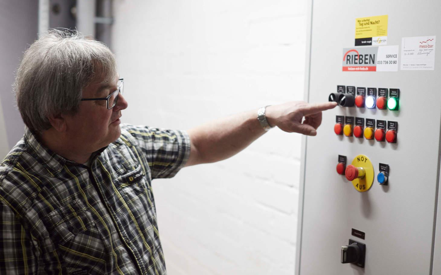 Jakob Baumgartner zeigt auf Knöpfe der neuen Heizung