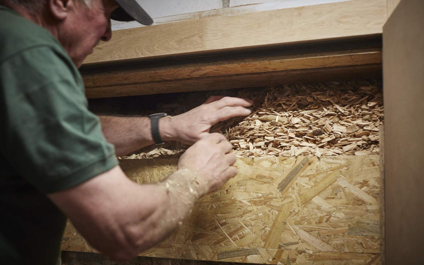 Handwerker füllt Holzschnitzel in die Heizungsanlage