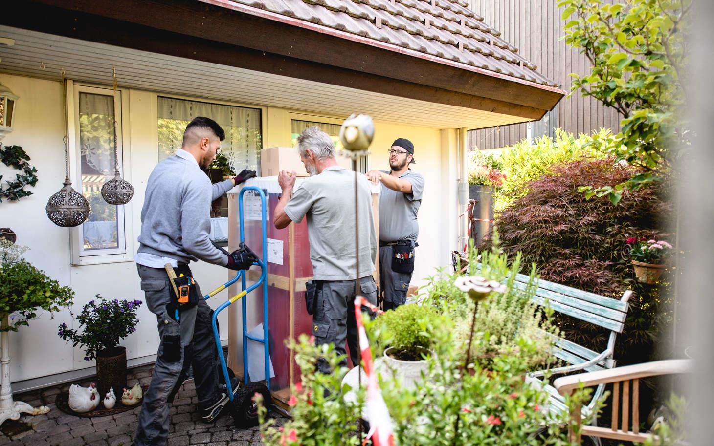 Handwerker laden das neue Heizzsystem ins Zälgli Haus