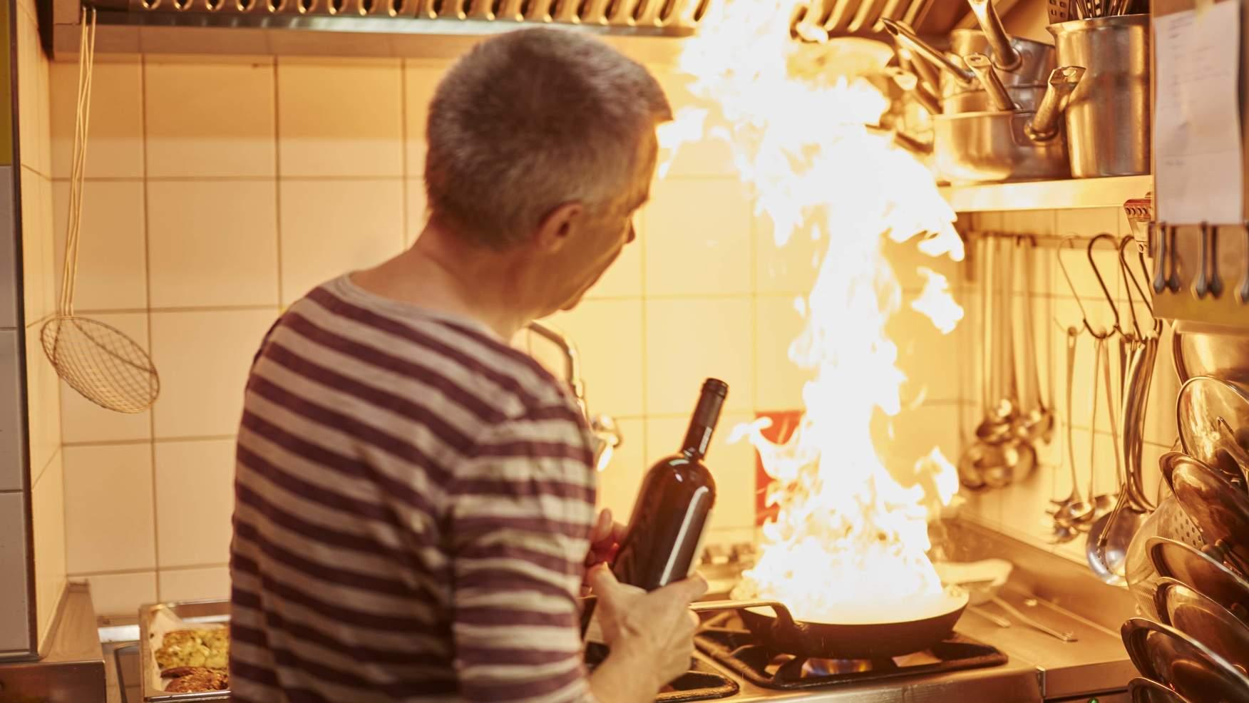 Koch flambiert das Essen mit Wein