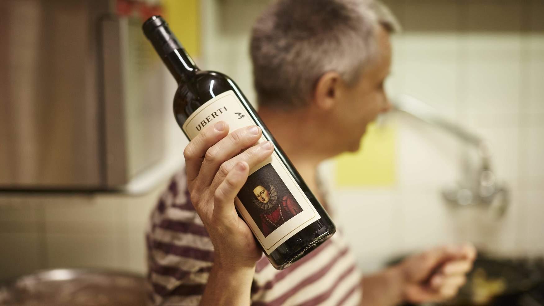 Mitarbeiter hält Weinflasche hoch