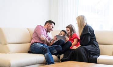 Familie sitzt mit Laptop auf Sofa