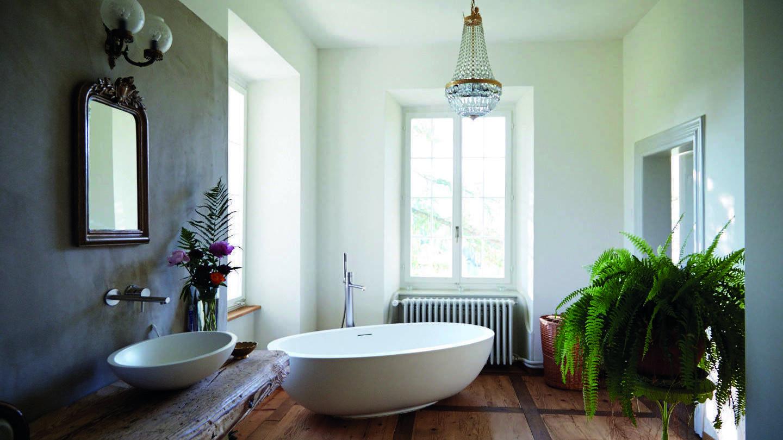 Badezimmer mit einer freistehenden Badewanne und Kronleuchter