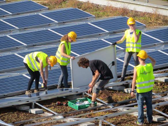 Schüler installieren Sonnenkollektoren auf dem Dach