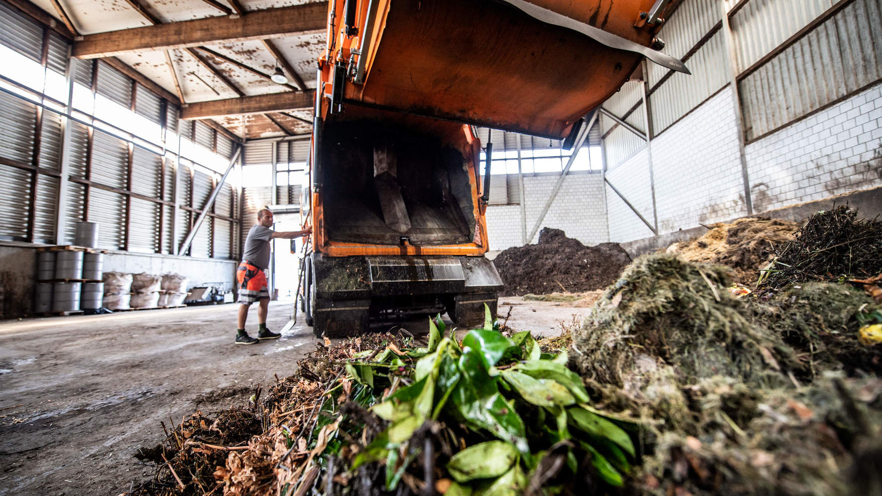 Handwerker entlädt Lastwagen in der Kompogasanlage