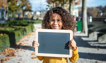 Mädchen steht lächelnd mit einer Tafel auf einem Weg